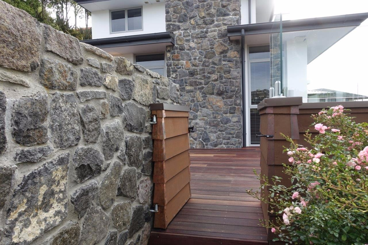 Rock wall with a gate beside