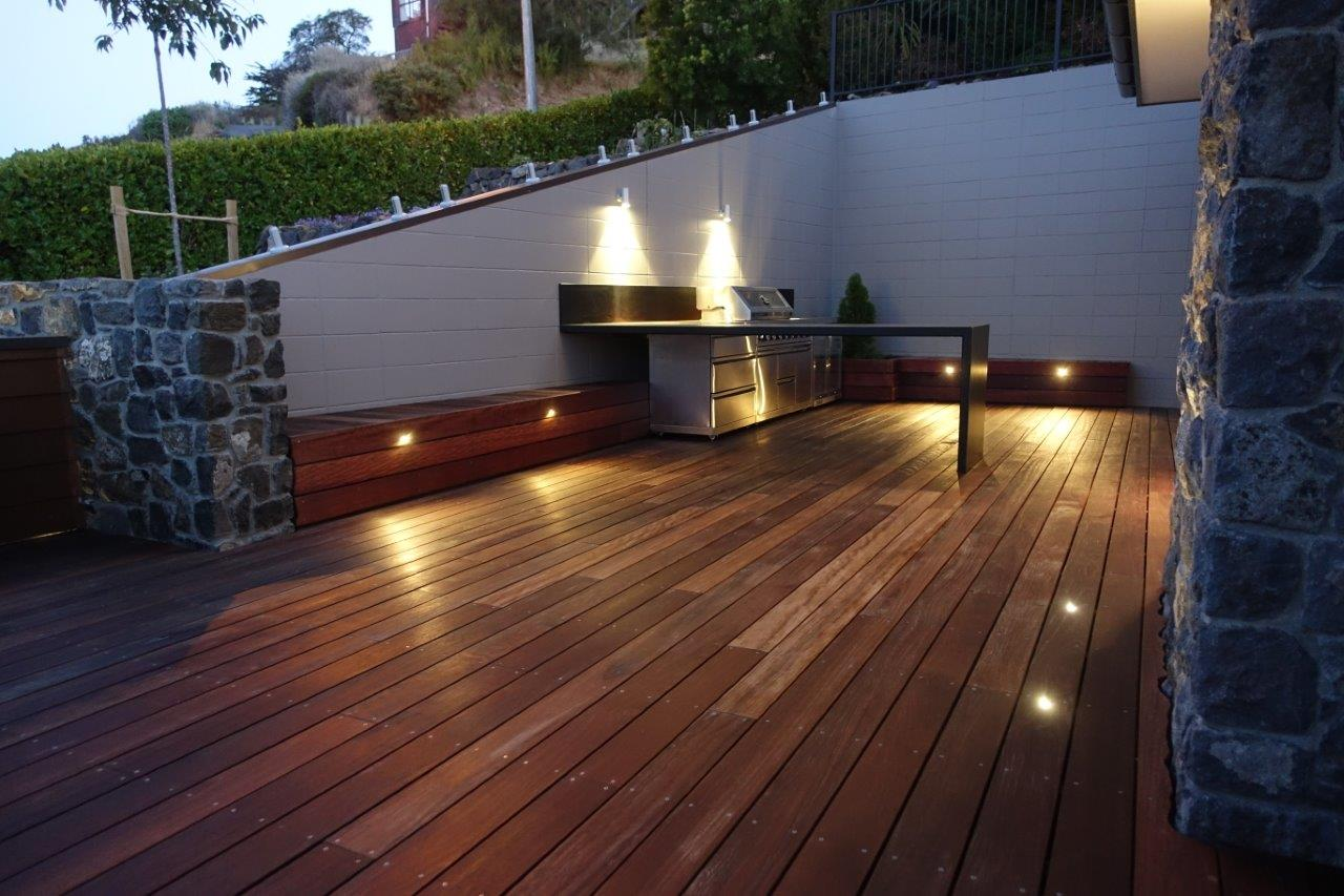 Landscaped outdoor living area with a deck and outdoor lighting