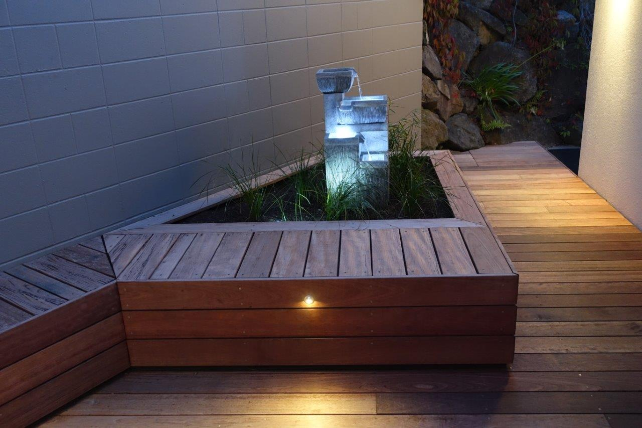 Landscaping: Raised planter box with a water feature inside surrounded by decking