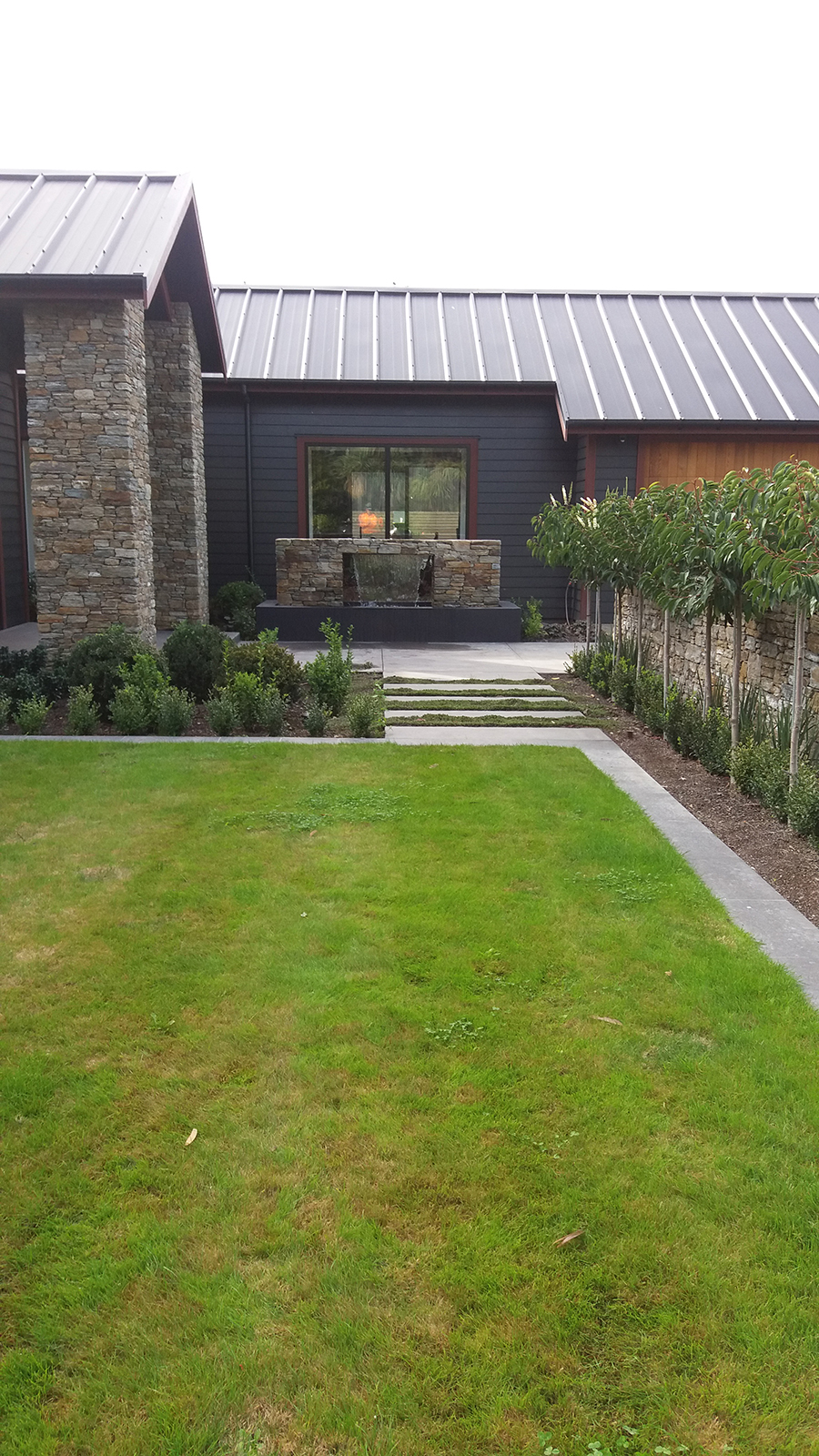 Water feature Landscaping with a lawn and garden either side