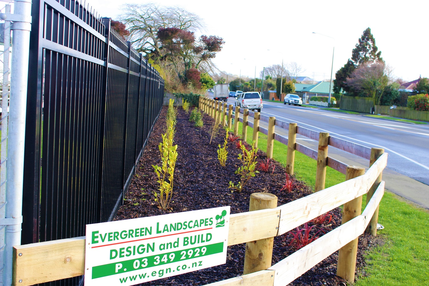 Front yard landscaping with a Evergreen landscapes sign