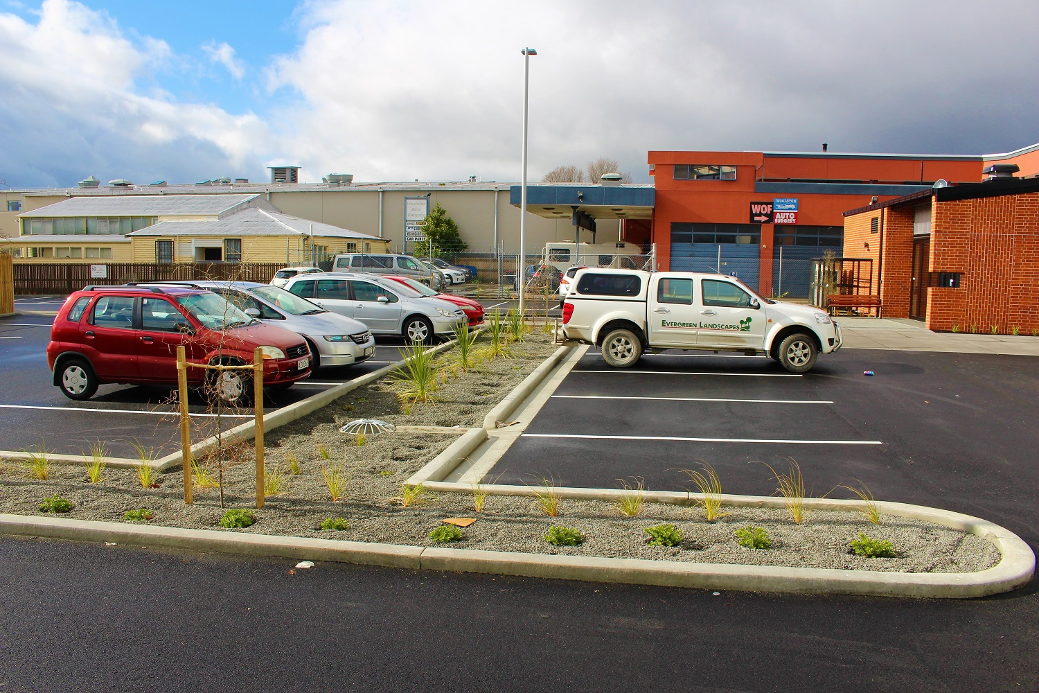 Landscaping in a car park with small pebbles, trees and plants in curbed garden bed