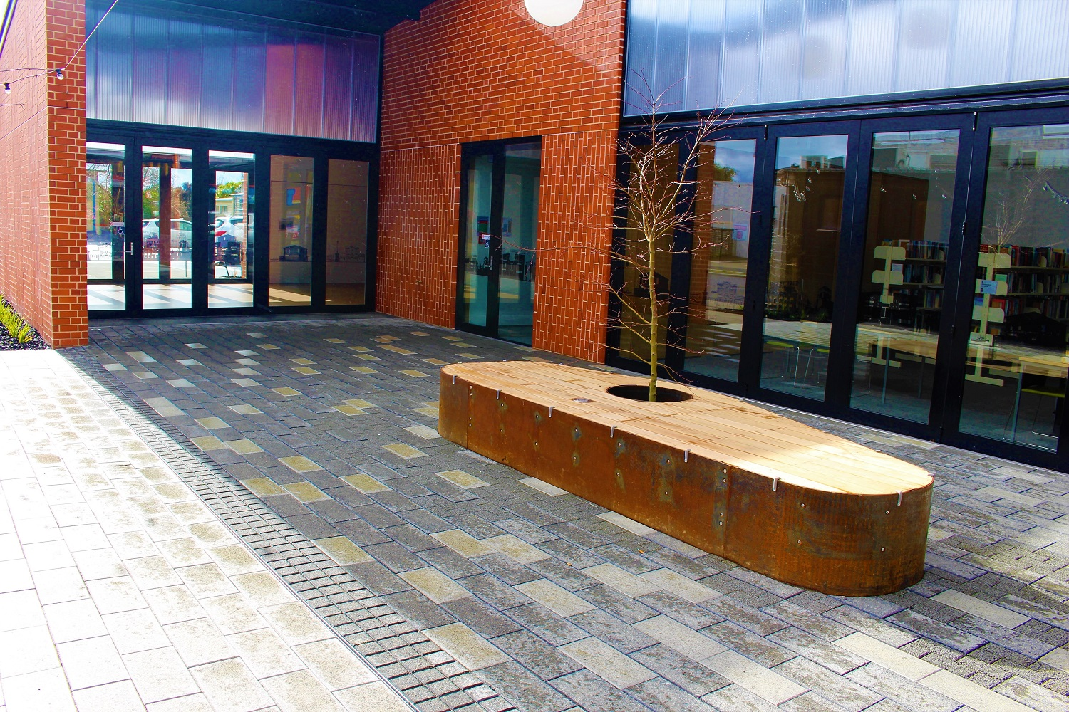 Courtyard with paving and a seat in the middle with a tree in it