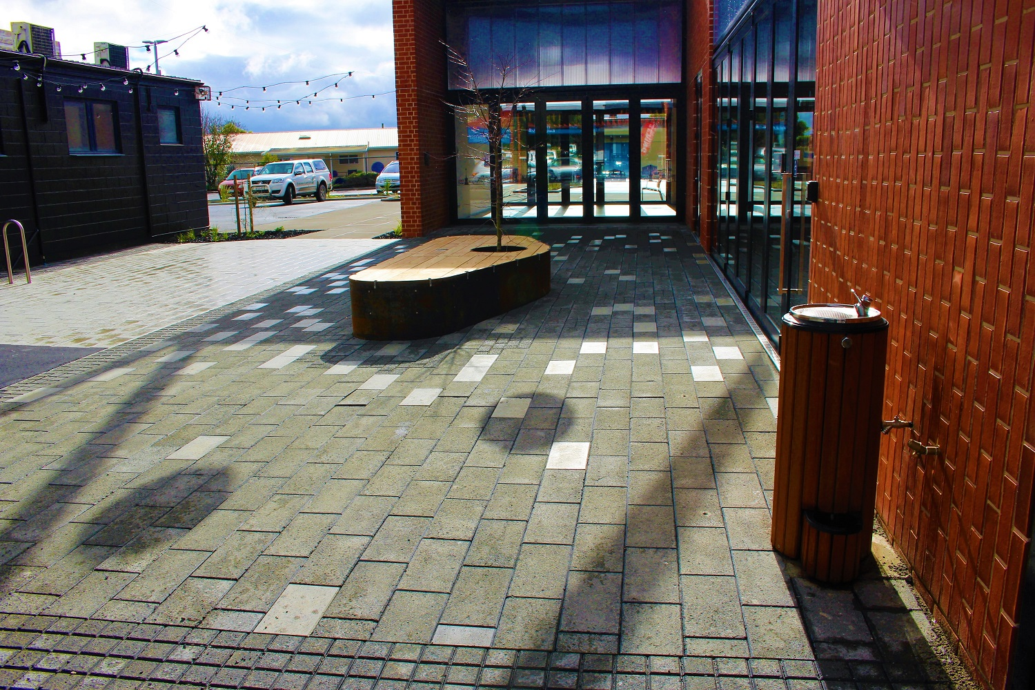 Commercial paving with a small white pavers dotted throughout. With a seat and water feature in as well.